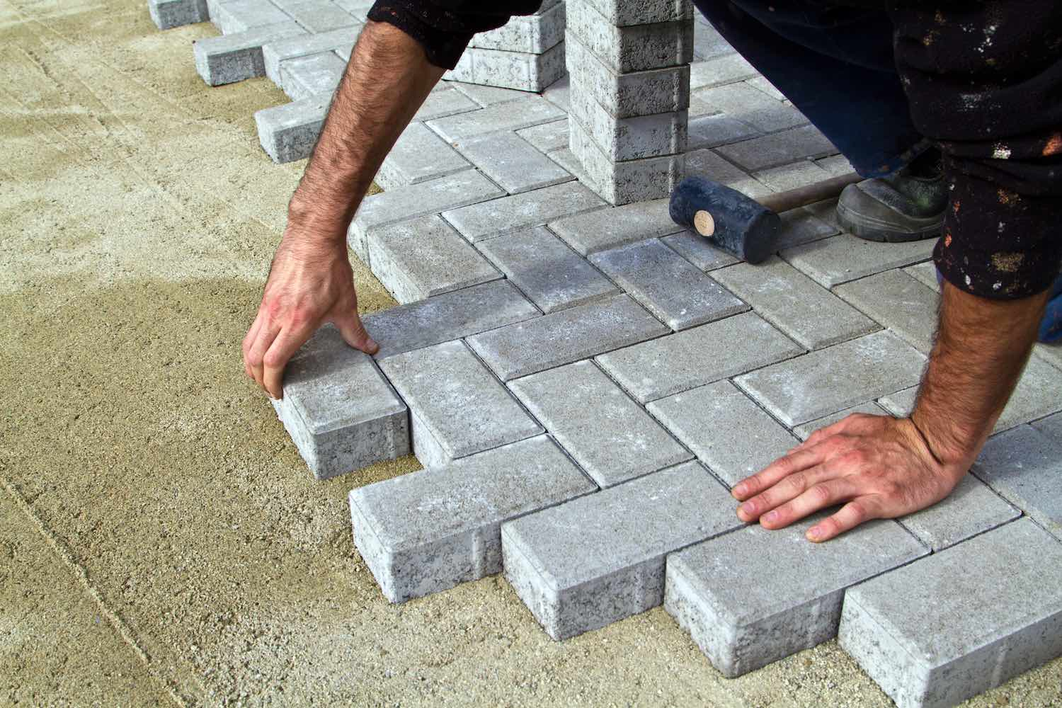 person laying down pavers